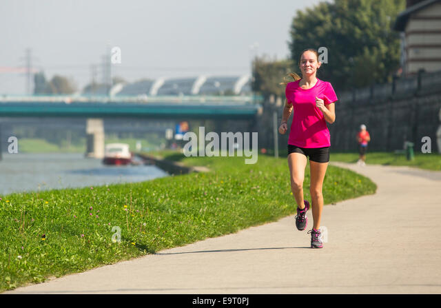Young girl jogging near the river embankment. Healthy lifestyle. - Stock Image