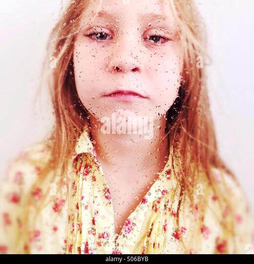 Portrait of a young girl behind a wet window. - Stock Image