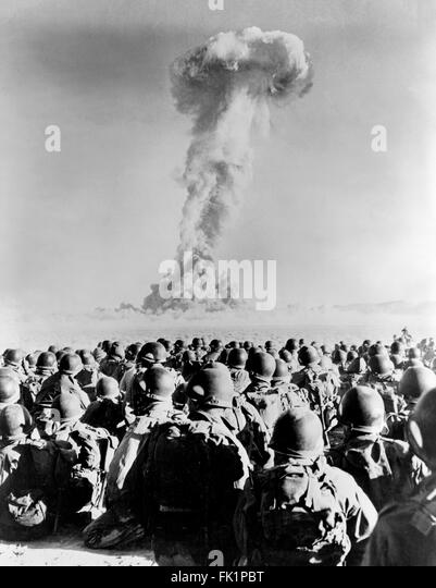 Nuclear Explosion. Troops from 11th AB Division in front of a  mushroom cloud from a nuclear test explosion at Frenchman - Stock Image