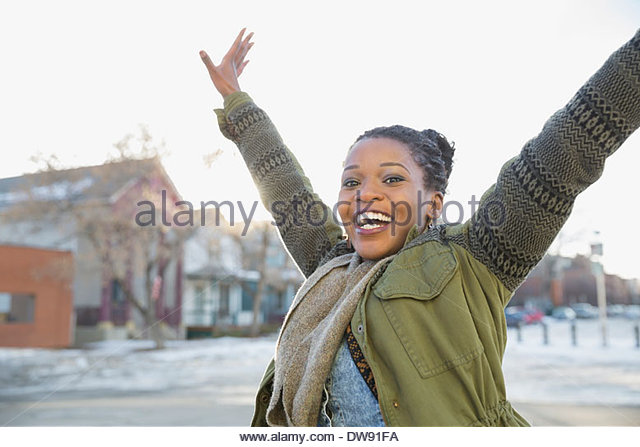 Excited woman with arms raised outdoors - Stock Image