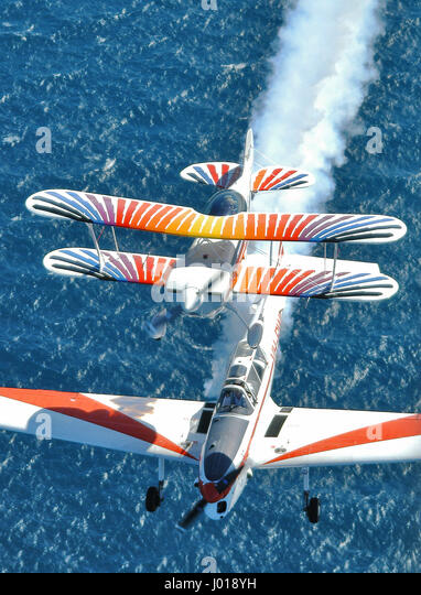 Aerial view of an aerobatic formation in training over the ocean, with smoke. DH Chipmunk and Christen Eagle aircraft. - Stock-Bilder