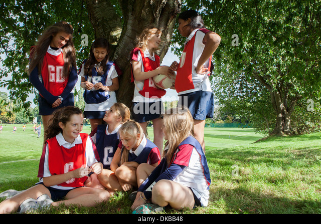 Teenage schoolgirl netball team taking a break - Stock Image