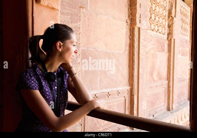 India, Jodhpur, Young woman looking through balcony - Stock-Bilder