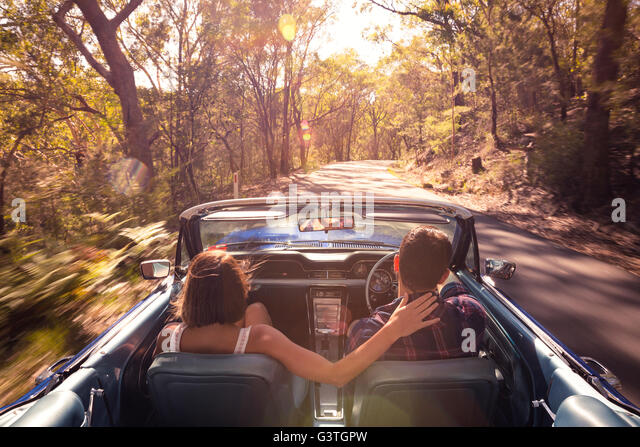Australia, New South Wales, Sydney, Lane Cove, Couple driving car through forest - Stock Image