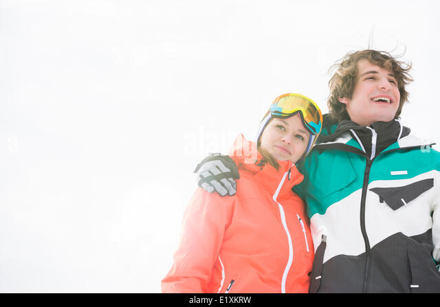Loving young couple in warm clothing against clear sky - Stock Image