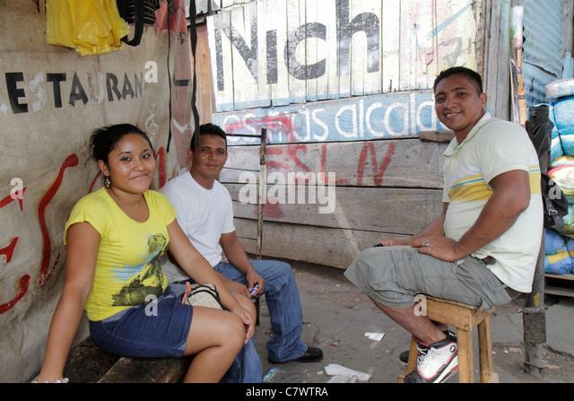 Nicaragua Managua Mercado Oriental market marketplace shopping stall shed Hispanic man woman young adult group sitting - Stock Image