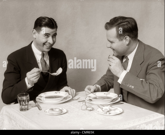 1930s TWO MEN DINING EATING SOUP SMILING - Stock Image