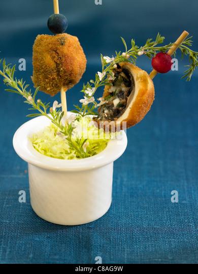 Mushroom balls coated with breadcrumbs on picks - Stock Image