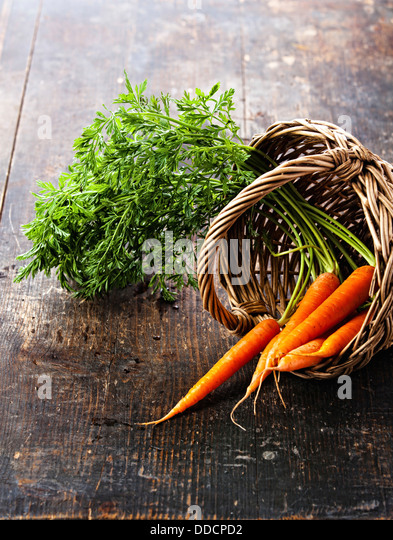 Fresh carrots in basket on wooden background - Stock Image