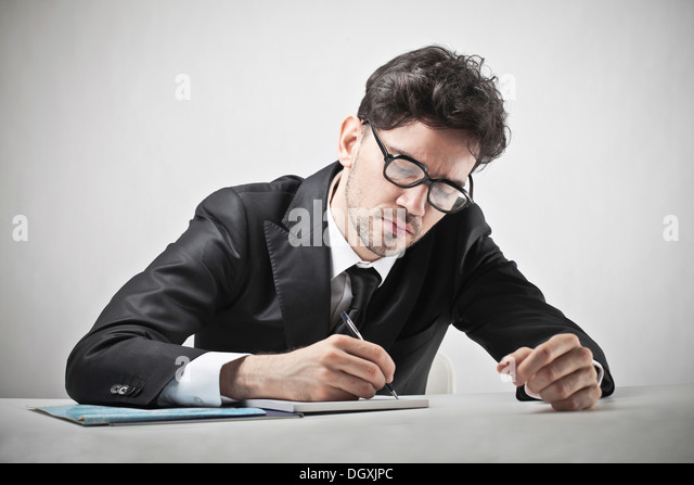 Young business with glasses writing on a notebook - Stock Image