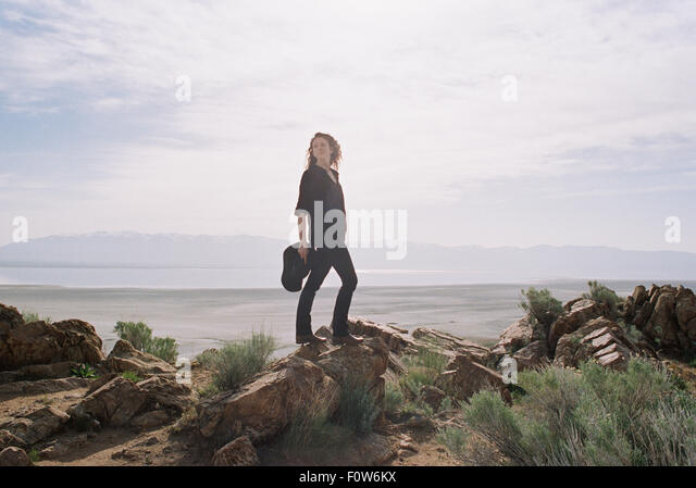 Woman with brown, long and curly hair standing on rocks, a lake and mountains in the distance. - Stock Image