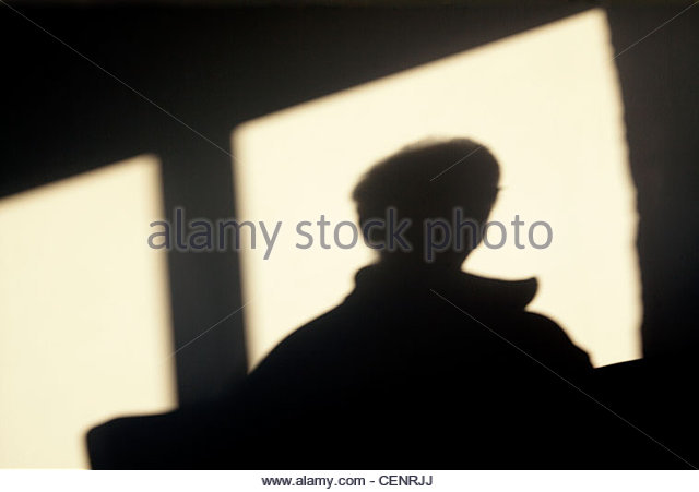 silhouette of a person looking out of a window - Stock Image