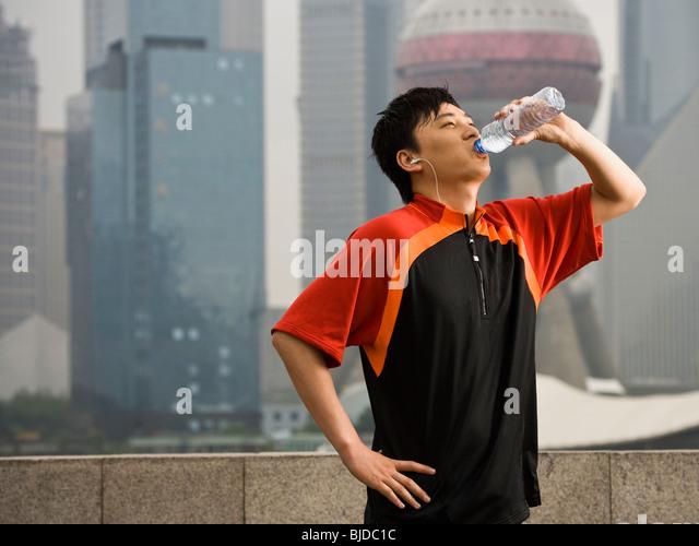 Man drinking bottled water. - Stock Image