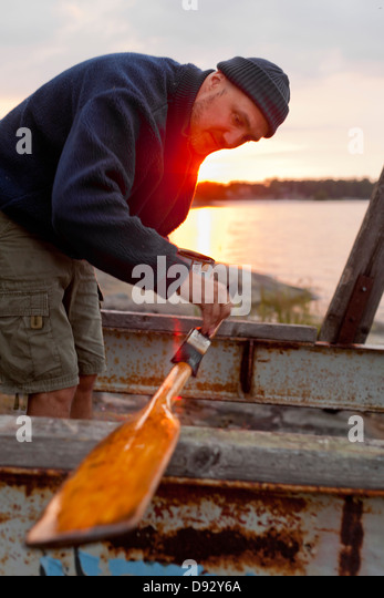 Man painting oar - Stock Image
