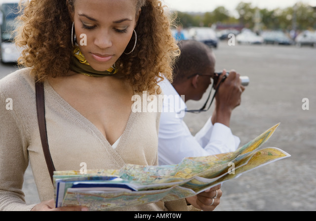 African woman looking at map - Stock-Bilder