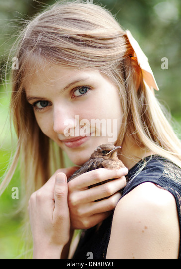 Girl with young bird on shoulder - Stock Image
