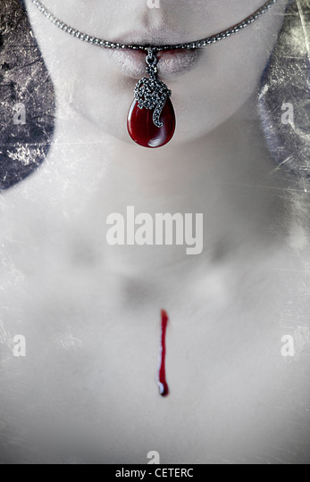 Close-up of pale female mouth and neck with necklace and drop of blood - Stock Image