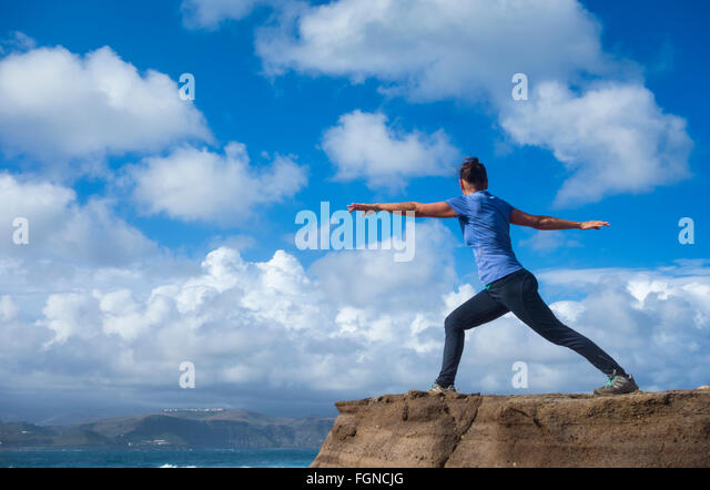 Mature female jogger warming up with Yoga stretching exercises on rock overlooking the sea. - Stock-Bilder
