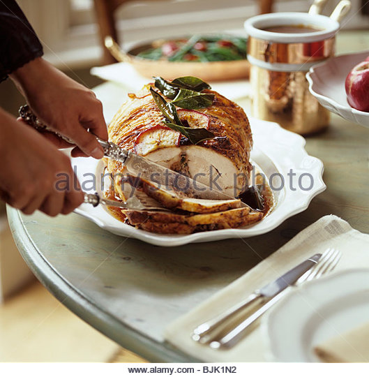 Stuffed roast pork being carved - Stock Image