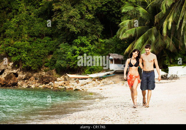 Smiling couple walking together on beach - Stock Image