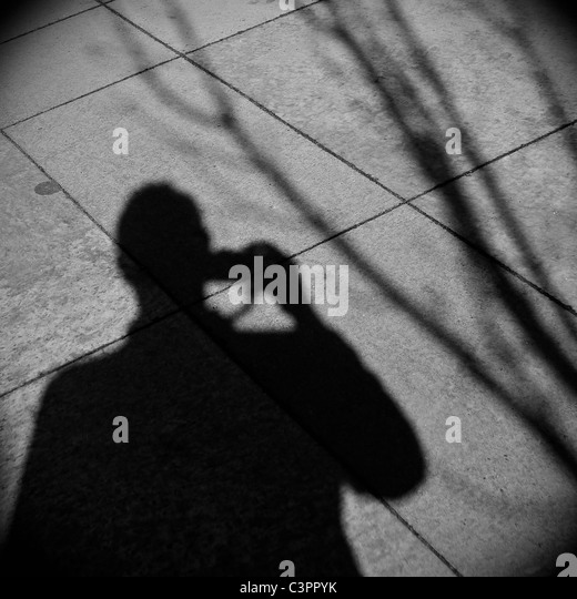 Shadow of man taking a photograph. - Stock Image
