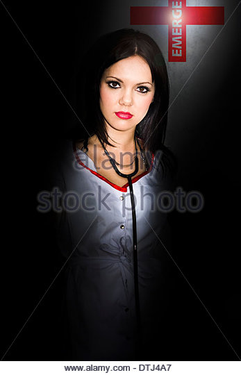 Health Image Of A Emergency Nurse Standing In The Darkness While On Late Night Shift Work At A Medical Hospital - Stock Image
