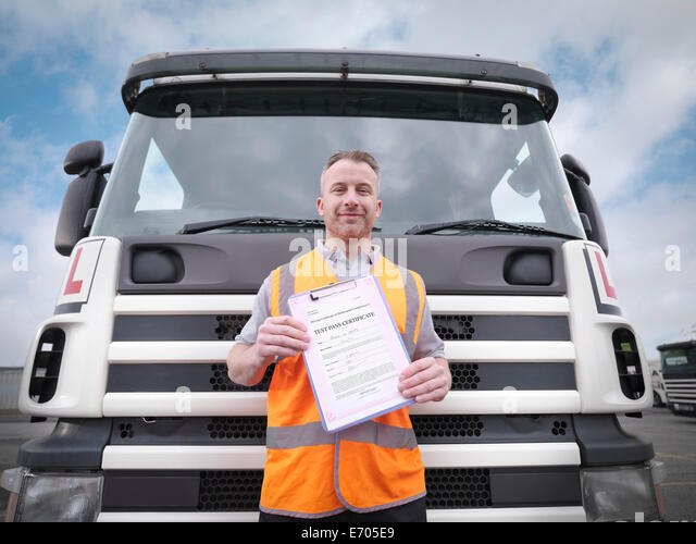 Portrait of trainee truck driver holding pass certificate - Stock Image