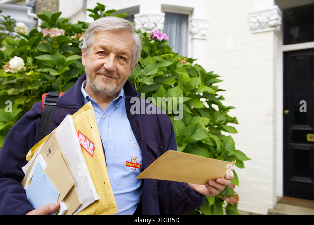 Royal Mail Postman routinely delivering letters, airmail, packages and parcels in residential area in the UK - Stock Image