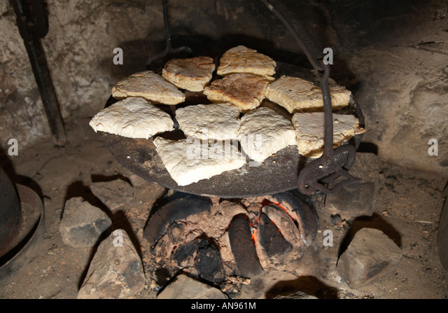 irish soda bread cooking on plate on traditional peat fire - Stock Image