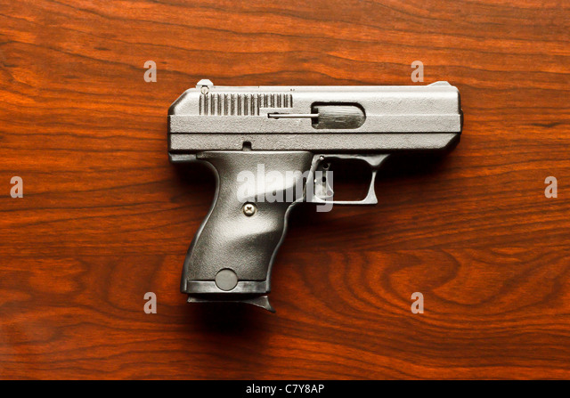 Top view of 9 mm handgun against wooden surface - Stock-Bilder