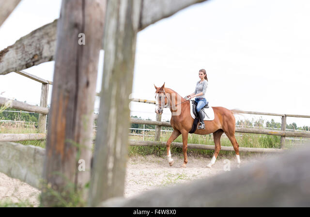 Woman horseback riding in fenced rural pasture - Stock Image