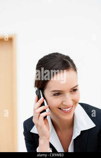Germany, Bavaria, Diessen am Ammersee, Young businesswoman talking on mobile phone, smiling - Stock-Bilder
