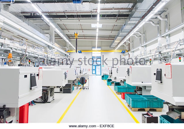 Empty factory production line with rows of work stations - Stock Image