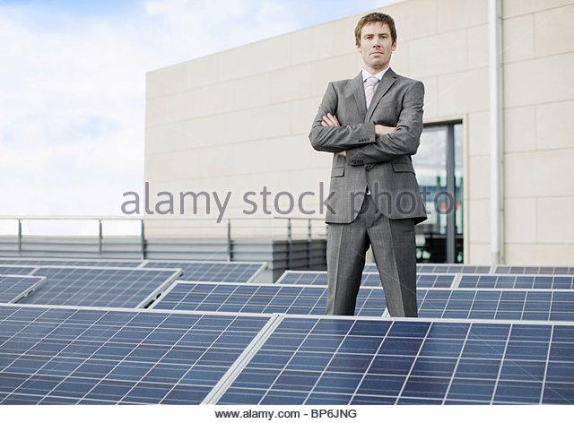 A businessman standing amongst solar panels - Stock Image