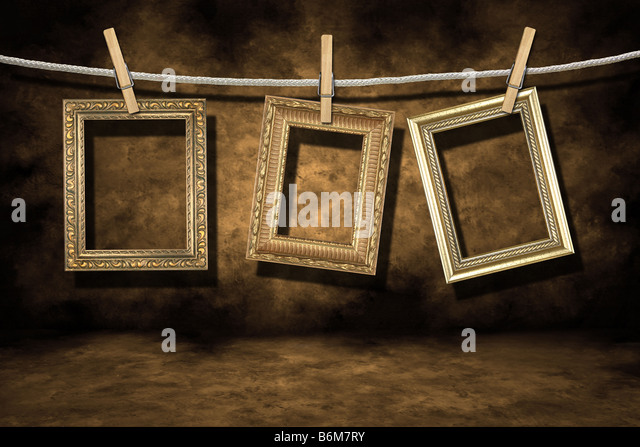 Blank Empty Gold Photo Frames on a Distressed Grunge Background Hanging on a Rope - Stock-Bilder