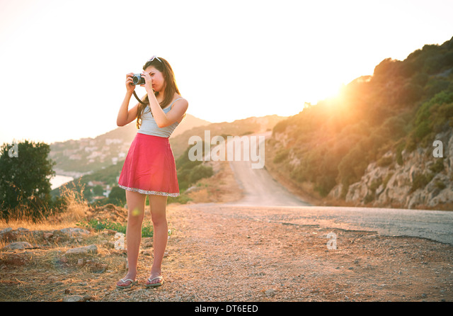 Girl taking photographs at sunset, Kas, Turkey - Stock Image