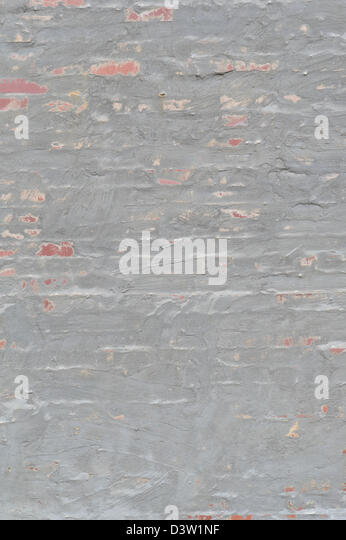 Wall of brick and gray stucco, close up of rough sandy uneven swirled finish, design element for backgrounds, textures - Stock Image
