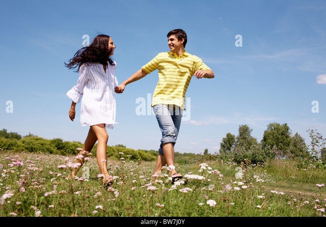 Portrait of woman and man holding by hands and walking over the glade - Stock Image