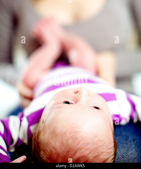 View from the top of the head of a tiny baby lying on its back on its mothers lap - Stock Image
