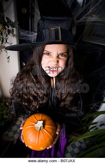 Girl in a witch's costume at a Halloween party, holding a pumpkin - Stock Image