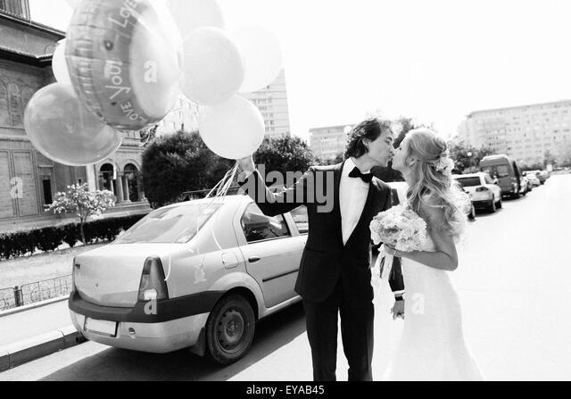 Young just married couple kissing on a street. Black and white image with grain film added as effect. - Stock Image