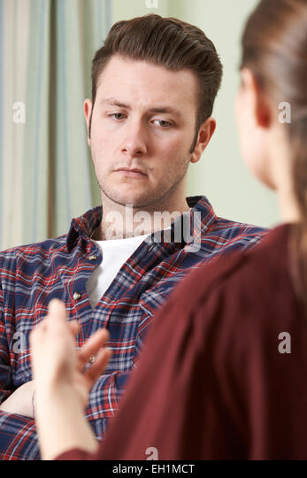 Depressed Young Man Talking To Counselor - Stock Image