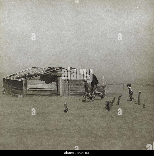 Storm in the Dust Bowl, America, 1930s. Man and boys walking towards wooden hut gradually being covered by wind - Stock Image