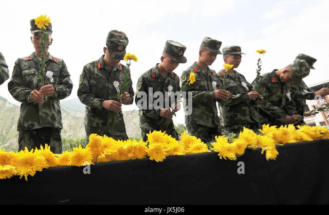 Jiuzhaigou, China's Sichuan Province. 15th Aug, 2017. Rescuers lay flowers during a mourning ceremony for victims - Stock Image