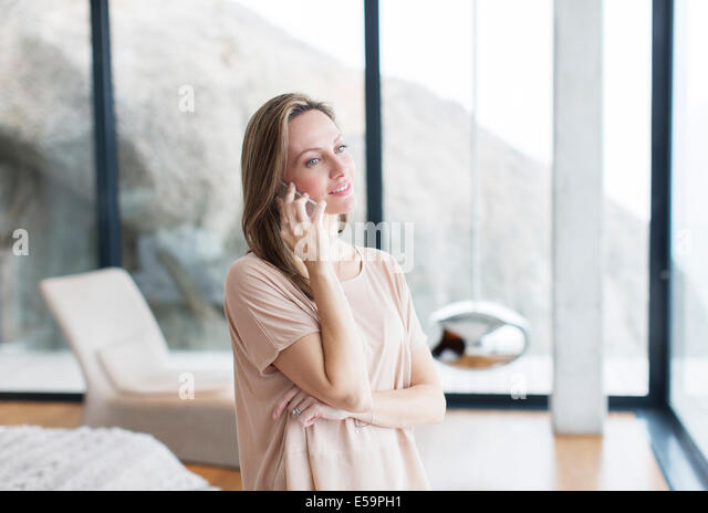 Woman talking on cell phone in modern living room - Stock Image