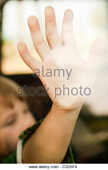 Hand of child touching car window - Stock Image
