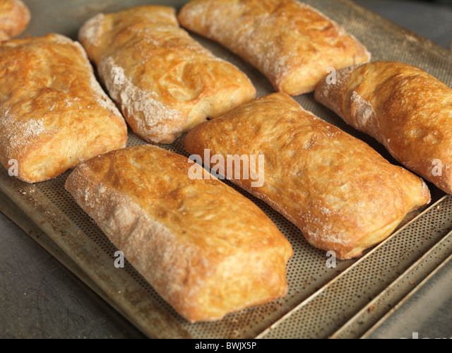 Freshly baked pastries on a baking tray - Stock Image