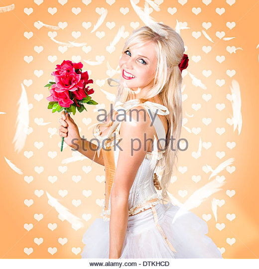 Delicate young woman holding flower bunch when celebrating valentines day with falling feathers - Stock Image