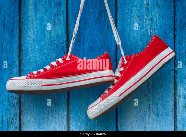 pair sneakers hanging on a wooden old retro blue background - Stock-Bilder