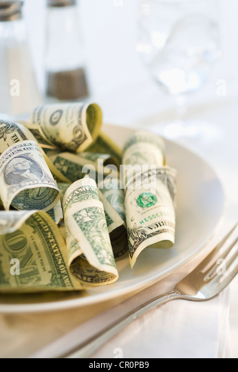 Paper currency on dinner plate, studio shot - Stock Image